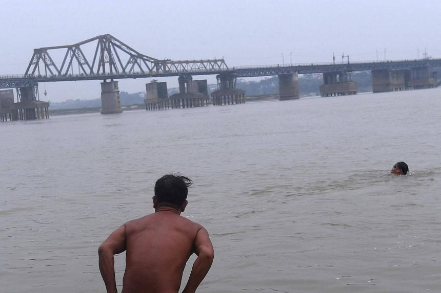 A nudist going for a swim in the Red River in Hanoi.