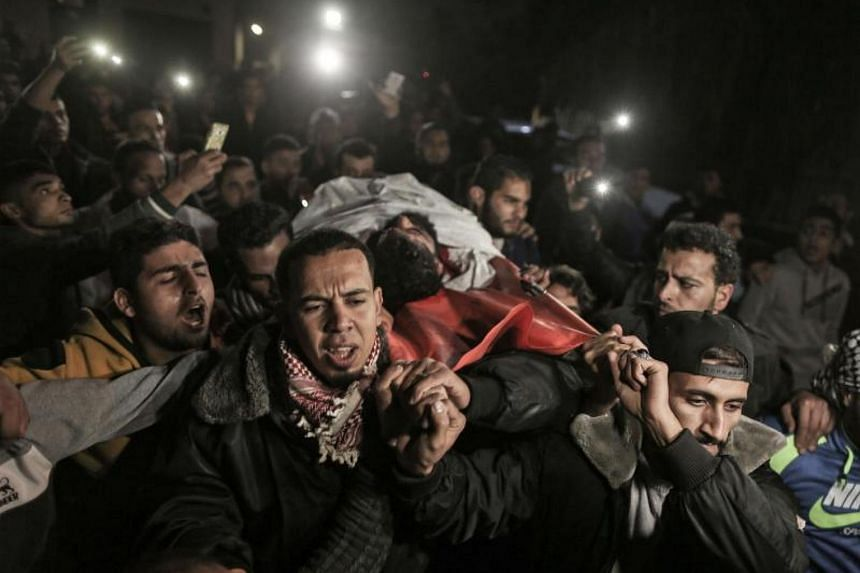 Palestinians carry the body of 29-year-old Ibrahim Abu Thurayeh into al-Shifa hospital in Gaza City on Dec 15, 2017 after he was shot dead in clashes between Israeli forces and protesters along the Gaza-Israel border.