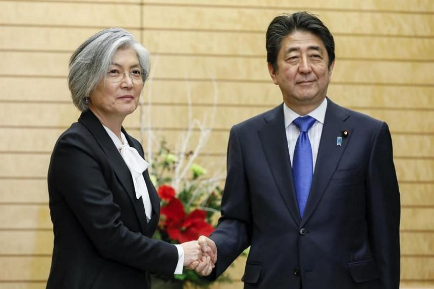 South Korean Foreign Minister Kang Kyung Wha (left) shakes hands with Japanese Prime Minister Shinzo Abe during her courtesy call at the latter's official residence in Tokyo, Japan, on Dec 19, 2017