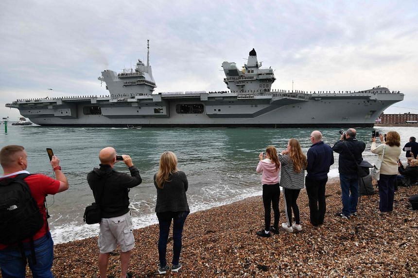 People watching as the Royal Navy carrier HMS Queen Elizabeth is manoeuvred into Portsmouth Harbour, on Aug 16, 2017.