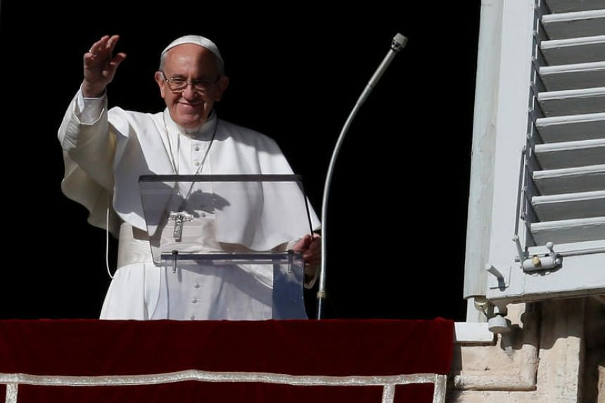 Pope Francis waves during his Sunday Angelus prayer, on the day of his birthday, in Saint Peter's square at the Vatican on Dec 17, 2017.