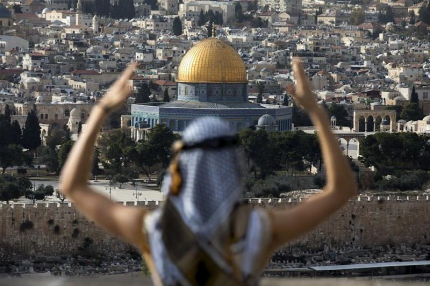 An American tourist views Jerusalem's walled Old City and the Temple Mount area, known to Muslims as Haram el-Sharif (The Noble Sanctuary) with its distinctive golden Dome of the Rock,  from the Mount of Olives in East Jerusalem, on Dec 18, 2017.