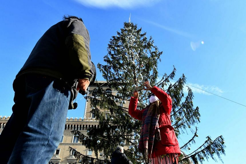 Tourists take pictures near the controversial Christmas tree at Piazza Venezia in Rome, Dec 19, 2017.