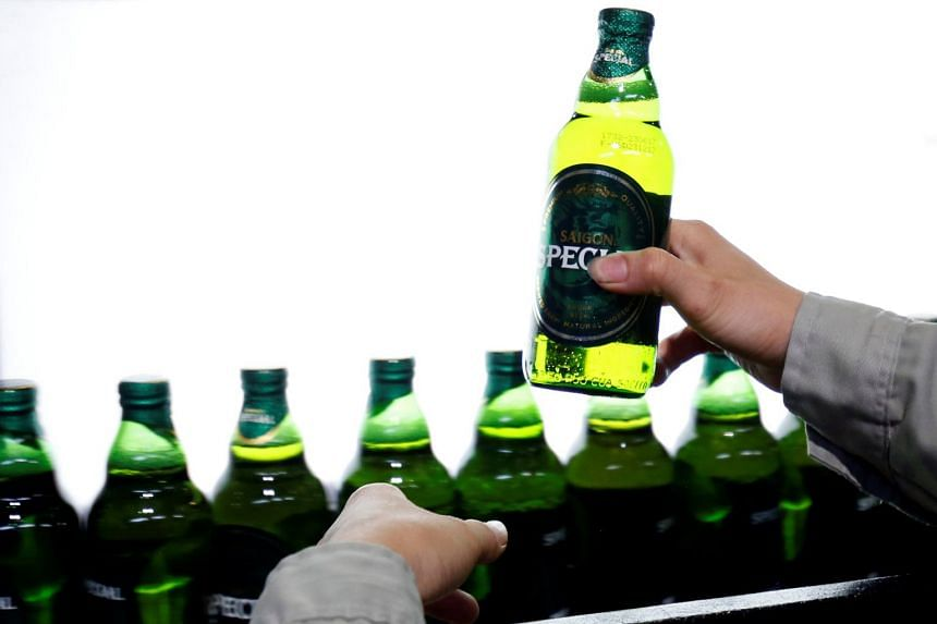 A worker checks for faults on beer bottles moving along a production line in a factory of Saigon Beer Corporation (Sabeco) in Hanoi, Vietnam.