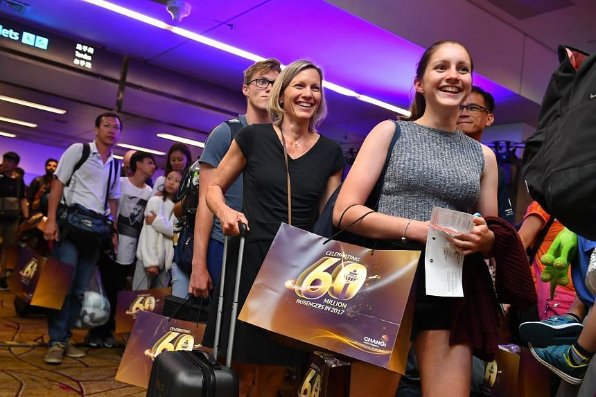 Passengers who had arrived at Singapore Changi Airport yesterday afternoon on Scoot Flight TR7 from Gold Coast, Australia, holding the goodie bags they received. They were also treated to champagne and a buffet. The rise in budget carriers is a reaso
