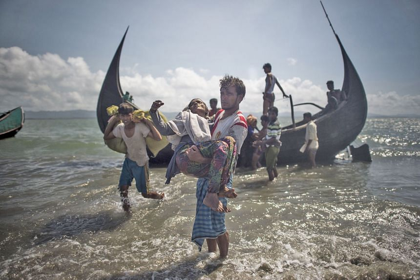 A Bangladeshi man helping Rohingya Muslim refugees to disembark from a boat in the Naf river after they crossed the border from Myanmar in September. Almost 870,000 Rohingya have fled to Bangladesh, including about 660,000 who arrived after Aug 25, w