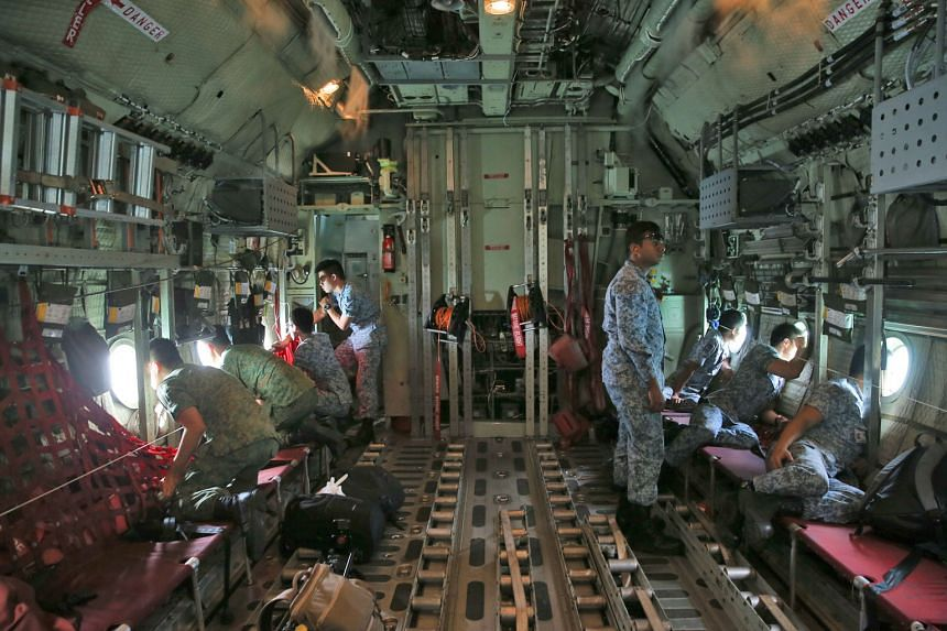 Republic of Singapore Air Force personnel on board a C-130, scanning the sea for the 10 missing sailors as the plane flew over the search area on Aug 23. The USS John S. McCain was left with a vast hole in its hull, after being involved in a collisio