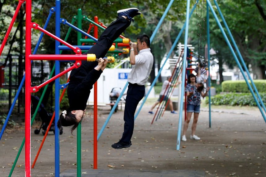 Office workers exercise during their lunch break at a park in central Tokyo.