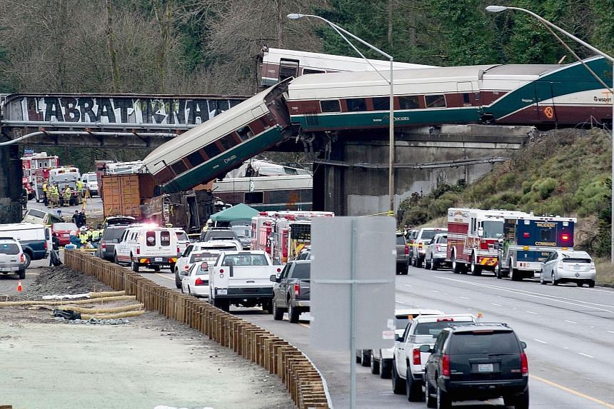 Emergency personnel near the derailed Amtrak train in DuPont, Washington. Thirteen of the train's 14 cars jumped the tracks. The scene at a portion of the Interstate I-5 highway after an Amtrak high-speed train derailed from an overpass on Monday. Th
