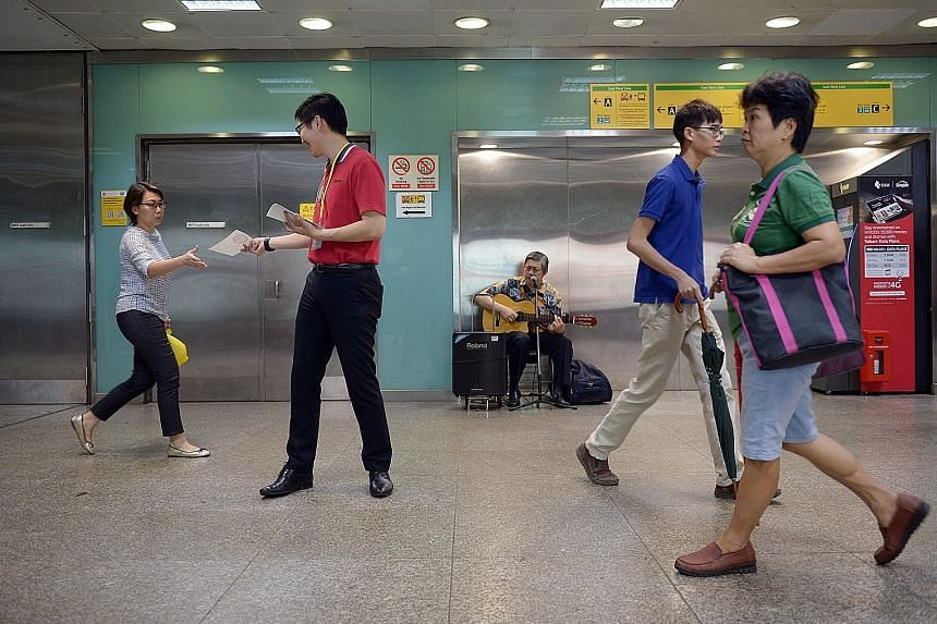 Above: Busking duo Ang Cheng Wei (left) and Er Young Yee performing at Bugis MRT station yesterday. Left: SMRT HR manager Adrian Gan, 35, giving out Christmas-themed stickers at the station, while busker Robert Tan performed Christmas songs.