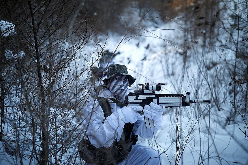 South Korean and United States Marines, in snow camouflage, take part in a winter military drill in the eastern mountainous region of Pyeongchang county, Gangwon, in South Korea yesterday. More than 400 marines from the two allies teamed up for the w
