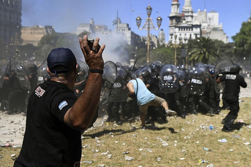 A stone-throwing demonstrator taking aim at riot police outside the Argentine Congress in Buenos Aires during a protest against proposed pension reforms on Monday. Protesters angry at proposed pension and welfare reforms by the centre-right governmen