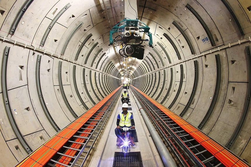 SP Group staff riding electric bicycles yesterday in the tunnel network of the Underground Transmission Cable Tunnel Project. Above them is a prototype model of an automatic inspection vehicle, the final version of which will be used to monitor the t