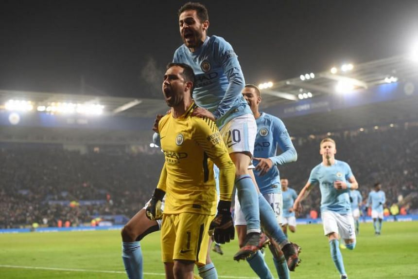 Manchester City's goalkeeper Claudio Bravo (left) celebrates with midfielder Bernardo Silva (second left) and other team-mates after winning the penalty shoot out during the English League Cup quarter-final football match against Leicester City on De
