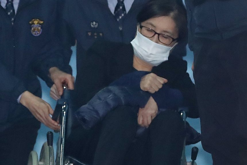 Choi Soon Sil, the central figure in ousted South Korean President Park Geun Hye's corruption scandal, is carried out in a wheelchair from the Seoul Central District Court on Dec 14, 2017.
