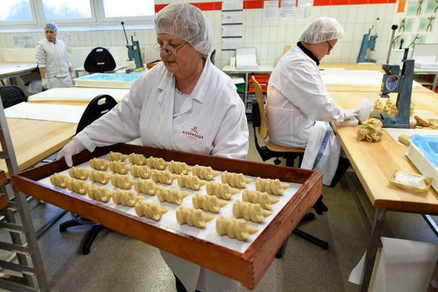Employees preparing pigs made of fresh marzipan at the headquarters of the traditional confectionary maker JG Niederegger GmbH in Luebeck, Germany.