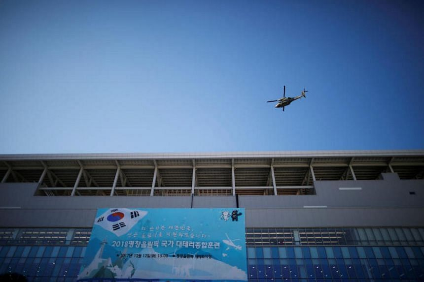 A South Korean army helicopter flies over the Olympic Stadium during a security drill ahead of the 2018 Pyeongchang Winter Olympic Games in Pyeongchan on Dec 12, 2017.