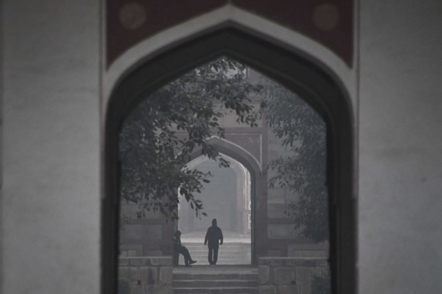 A man walks early in the morning amid heavy smog at Humayun's Tomb in New Delhi, on Dec 6, 2017.