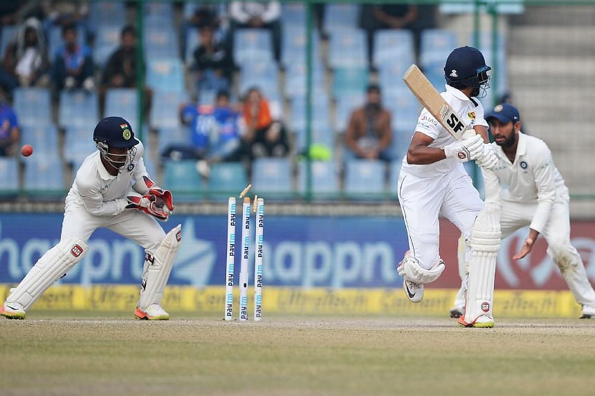 Sri Lanka team captain Dinesh Chandimal (centre) is bowled by Indian bowler R. Ashwin (not pictured) during the fifth day of the third Test cricket match between India and Sri Lanka, on Dec 6, 2017.