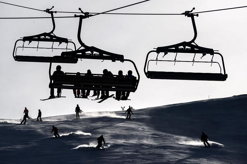 Skiers sitting in a ski lift as others ski down a slope in the Swiss Alps resort of Les Crosets.