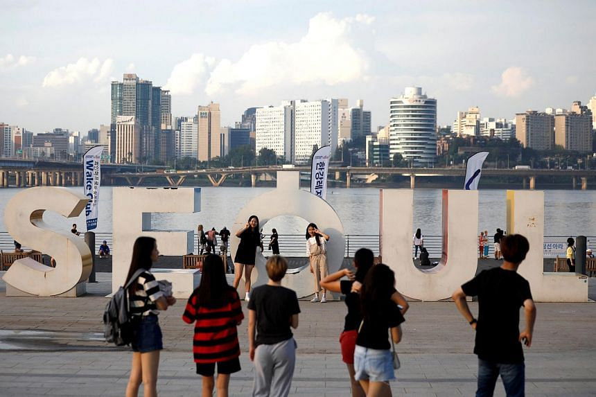 Tourists pose for photographs at the Han river park in Seoul.