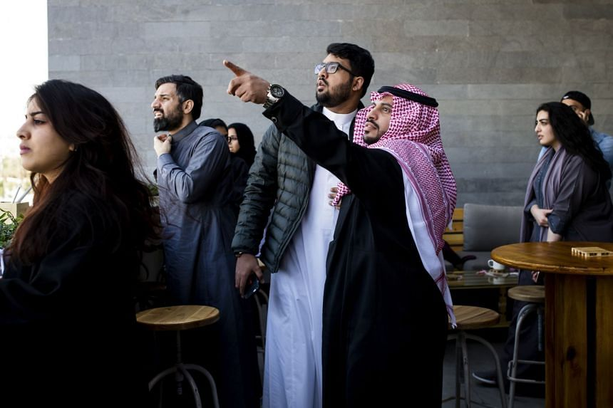 Customers at a coffee shop look at a cloud of smoke in the sky after a loud boom in Riyadh, Saudi Arabia.
