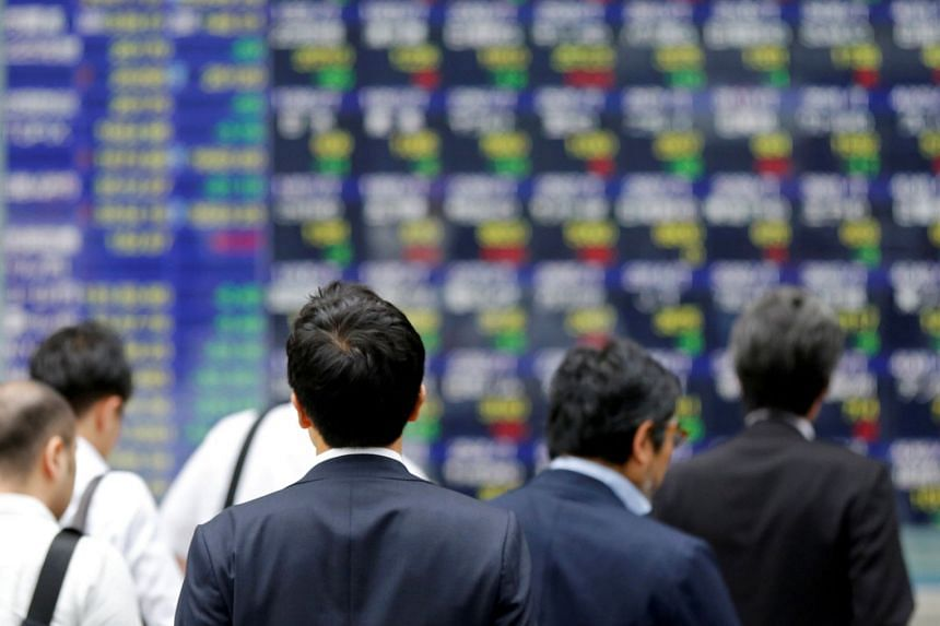 People walk past an electronic stock quotation board outside a brokerage in Tokyo.