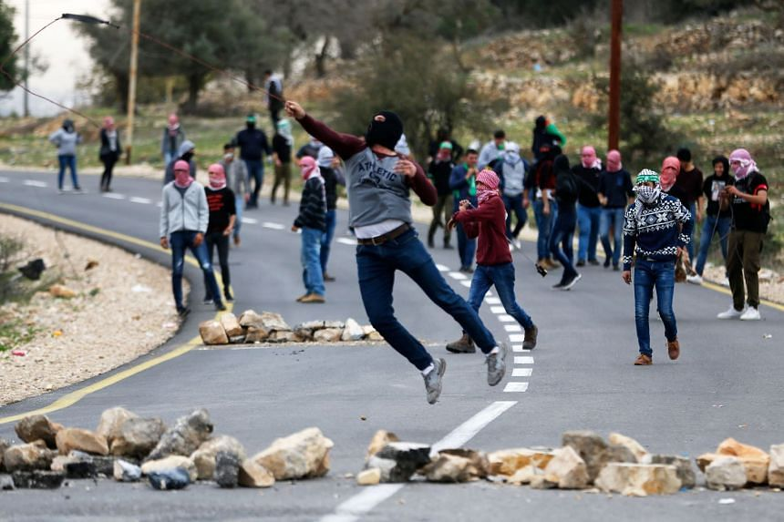 A Palestinian protester throws stones towards Israeli security forces during clashes at Atarot checkpoint on the northern outskirts of Jerusalem, Dec 19, 2017.