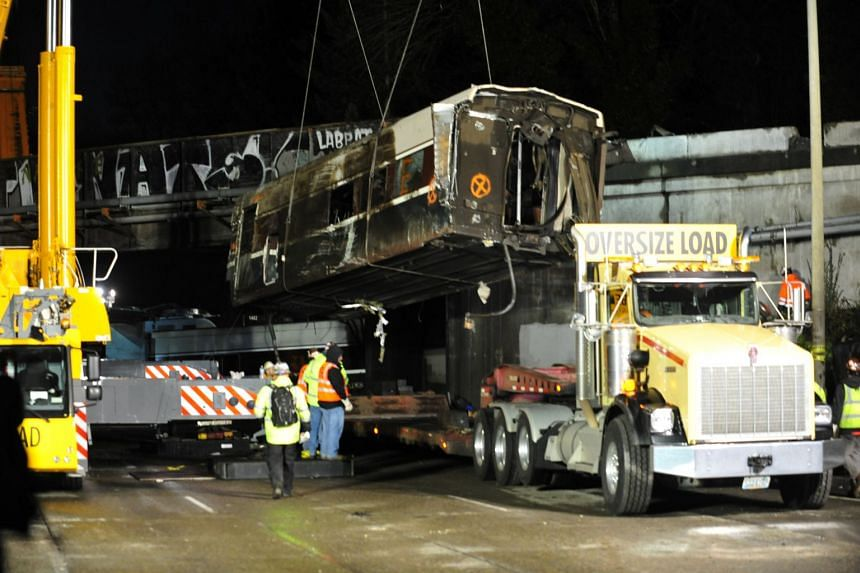 A damaged Amtrak passenger train car is lifted from the tracks at the site of the derailment, Dec 19, 2017.