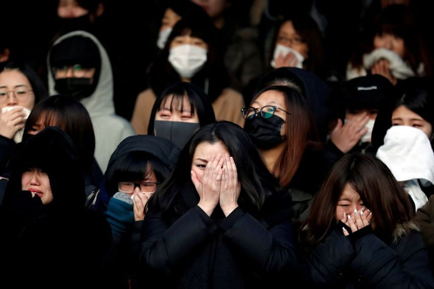 Fans of SHINee's Kim Jong Hyun react as a hearse carrying his coffin leaves during his funeral at a hospital in Seoul.