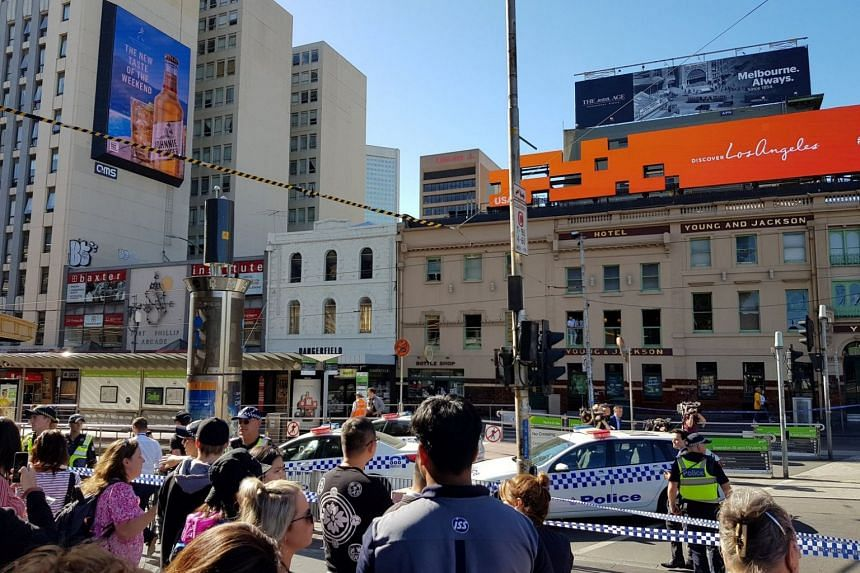 Emergency cars are seen on the street following the incident outside Flinders Street Station.