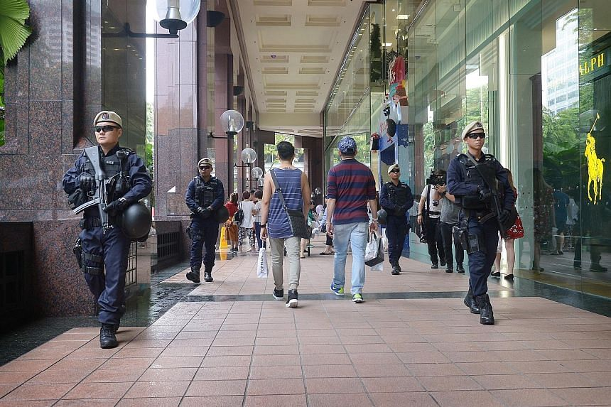 Protective Security Command officers on patrol at Ngee Ann City mall in Orchard Road last week. The shopping belt will be among areas where crowd control measures will be deployed on Christmas Eve and Christmas Day. The police advise the public to co