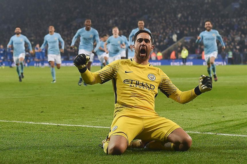 Manchester City players rushing to celebrate with their Chilean goalkeeper Claudio Bravo, after he saved the final Leicester penalty for them to win the League Cup quarter-final shoot-out.