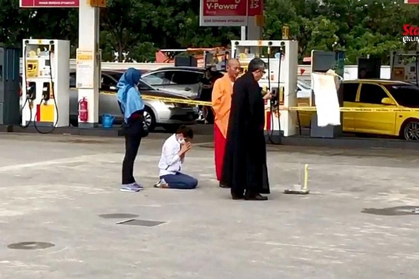 Mr Tan Ah Choy's widow (kneeling) and two Buddhist monks were seen on Tuesday offering prayers at the petrol station in Taman Pelangi, Johor Baru, where the killing took place. Police investigations are going on, including whether the murder was moti