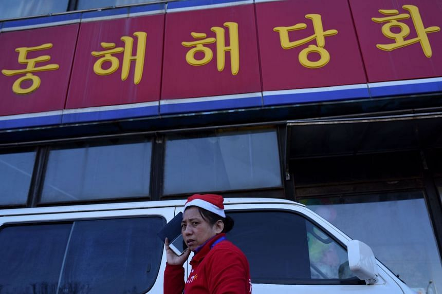 A sales promoter of a supermarket uses her mobile phone as she walks past a North Korean restaurant in Beijing on Dec 20.