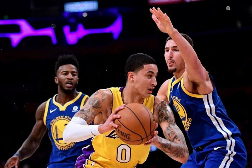 Kyle Kuzma of the Los Angeles Lakers drives on Golden State Warriors' Klay Thompson and Jordan Bell