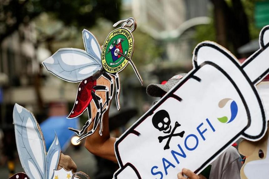 People hold banners in front of Sanofi Pasteur's office building during a protest in Makati, south of Manila on Dec 18, 2017.