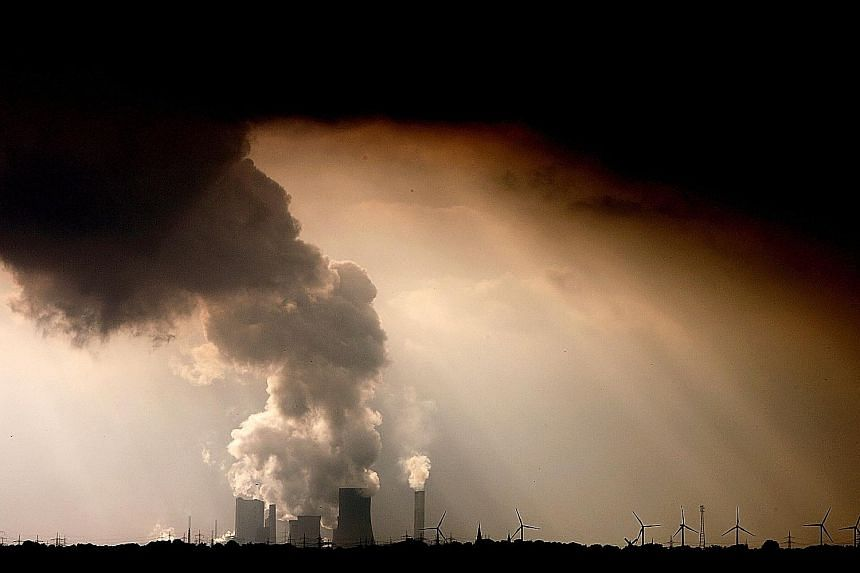 Smoke and vapour rising from the cooling towers and chimneys of a power plant near Bergheim in Germany in 2009. The KPMG survey found that only 17 per cent of Singapore firms have set carbon reduction targets, which pales in comparison to the global