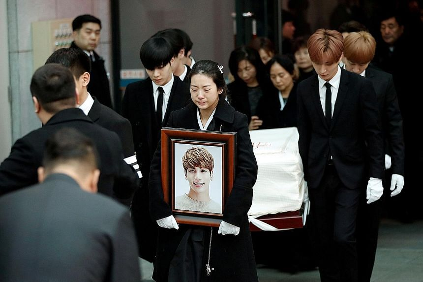 "Kim Jong Hyun's SHINee bandmate Minho bearing a plaque topped with a cross and reading ""Kim Jong Hyun, believer"". Fans of Kim, the lead singer of top South Korean boyband SHINee, weep as a hearse carrying his coffin passes by. Kim's sister, tears cou"