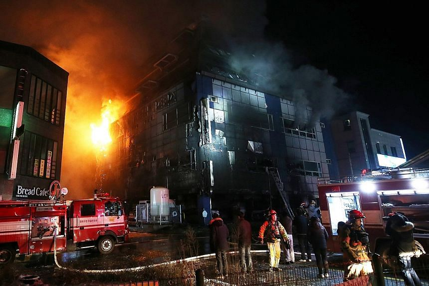 Television footage showed the building consumed by orange flames and issuing dark plumes of smoke. Some people were seen jumping from the building onto air mattresses laid out on the ground.