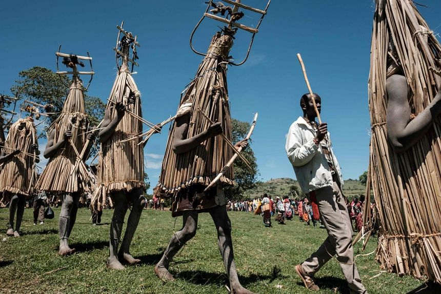 Circumcised Maasai young men in ritual costumes adorned with birds they hunted emerging from the bush near Kilgoris, Kenya, on Wednesday to receive blessings to mark the end of the annual month-long circumcision ceremony. As a rite of passage, the 18