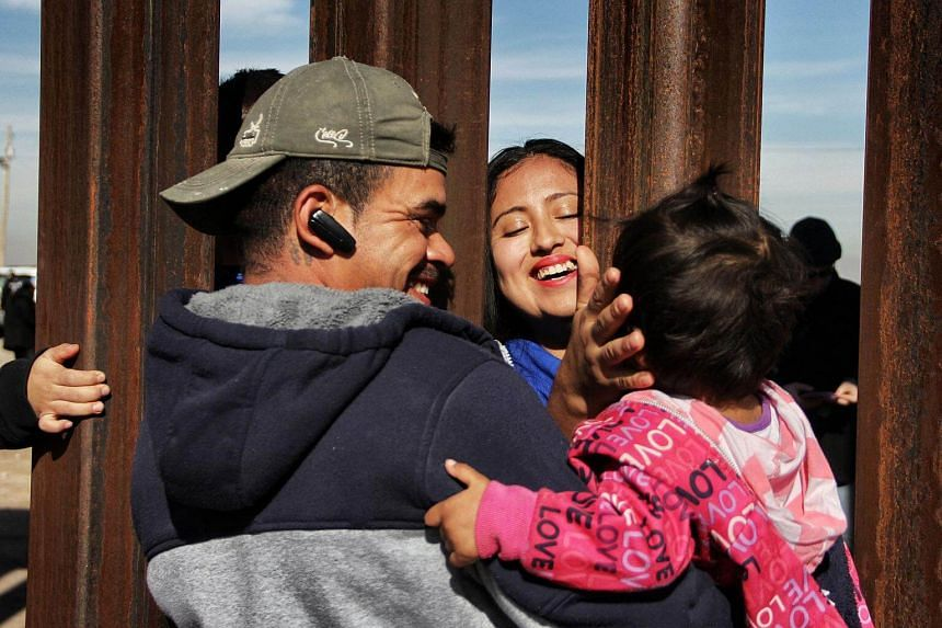 Members of a family reunite through the border wall between Mexico and United States, during an event, in Ciudad Juarez, Chihuahua state, Mexico, on Dec 10, 2017.