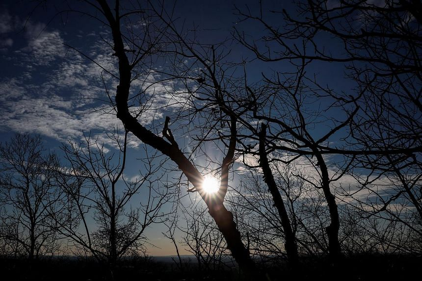 The sun sets in the afternoon on the winter solstice, as seen from atop Clausland Mountain County Park near the Hudson River Palisades, in Orangeburg, New York, on Dec 21, 2017.