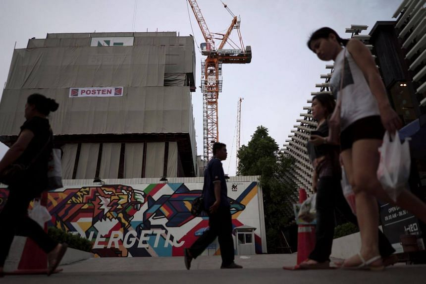 People walk past an under-construction site of a condominium in Bangkok, Thailand.