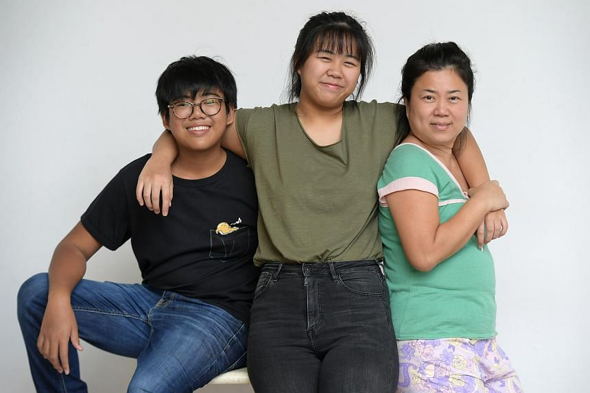 Christel Phouthavong (centre) and her younger brother Bentley (left) with their mother  Calisa Cheong. The siblings received $350 each in bursaries from non-profit Industrial & Services Cooperative Society.