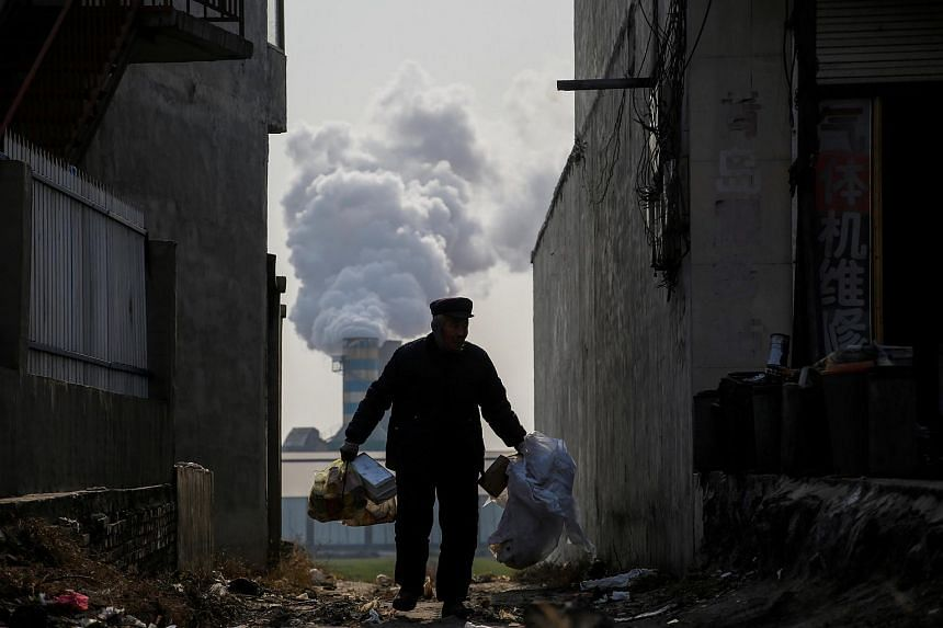 A man collects recyclables from an alley as smoke billows from the chimney of a factory in rural Gaoyi county, known for its ceramics production, in China's Hebei province on Dec 7, 2017.