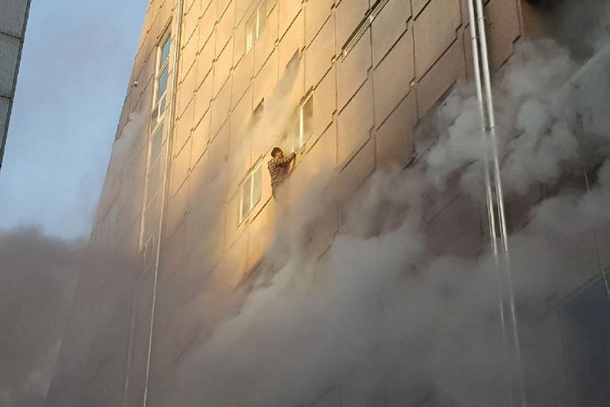 A survivor dangles from a windowsill as he waits for rescue from the burning building in Jecheon, South Korea, on Dec 21.