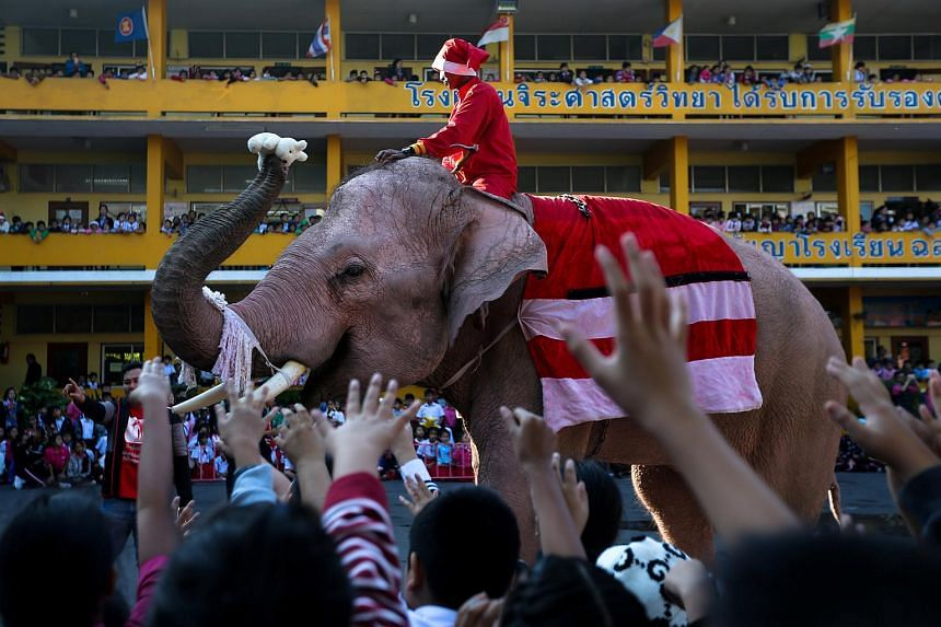 An elephant dressed in a Santa Claus costume distributing a doll to students during Christmas celebrations at Jirasartwitthaya School in Ayutthaya, Thailand, on Dec 22, 2017.