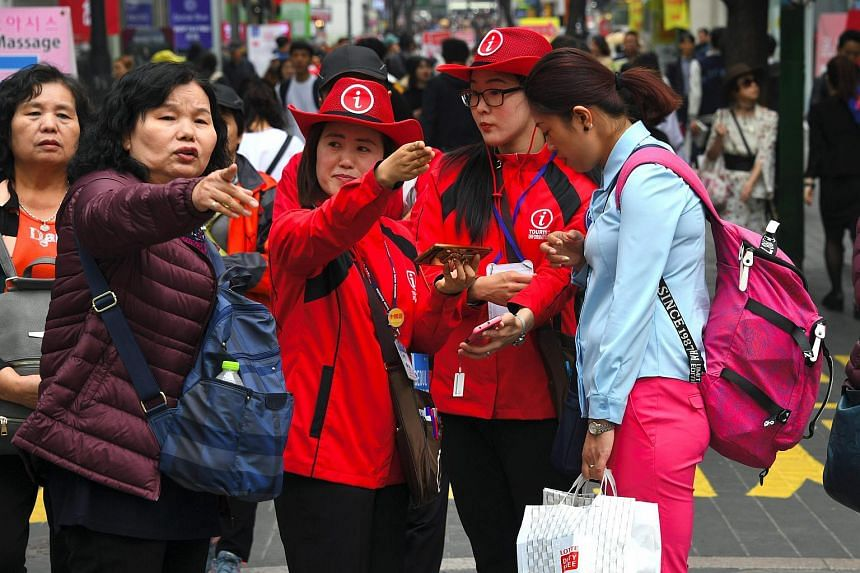 South Korean tourist information helpers guide tourists in the popular Myeongdong shopping district in Seoul.
