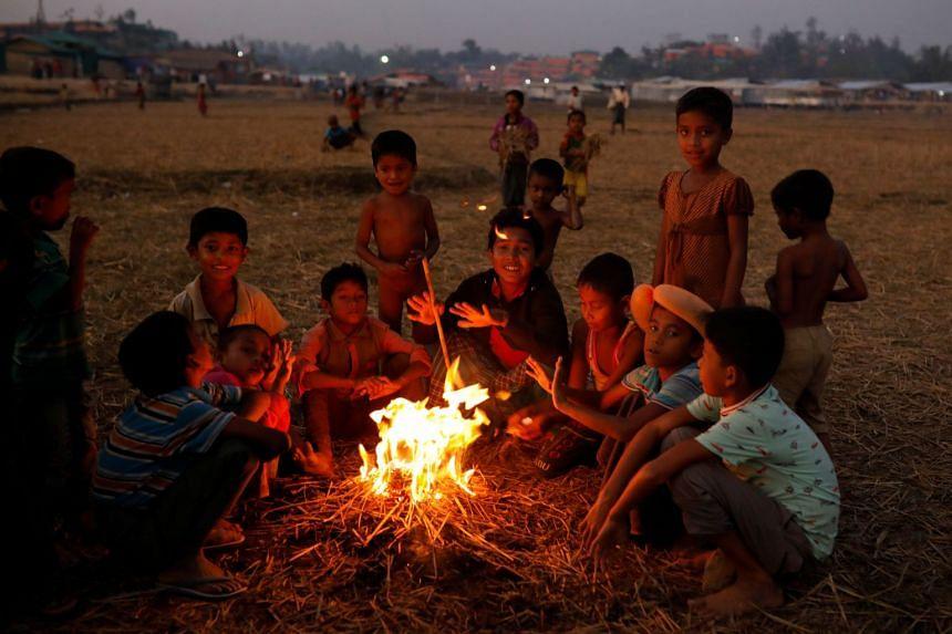 Rohingya refugee children sit around a fire at the Palongkhali refugee camp near Cox's Bazar, Bangladesh.